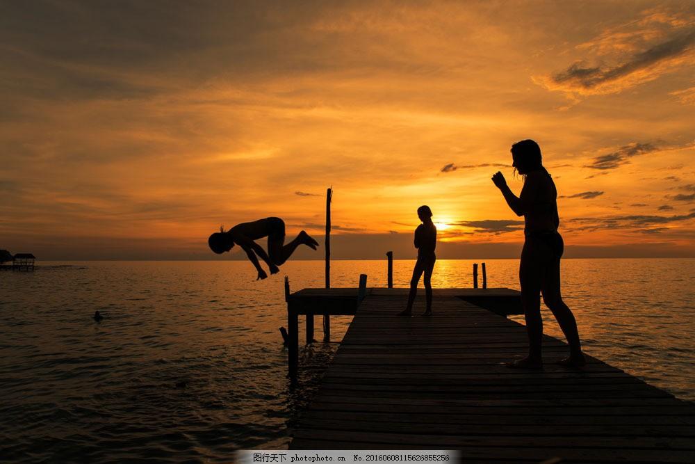 海邊黃昏下的人物剪影圖片