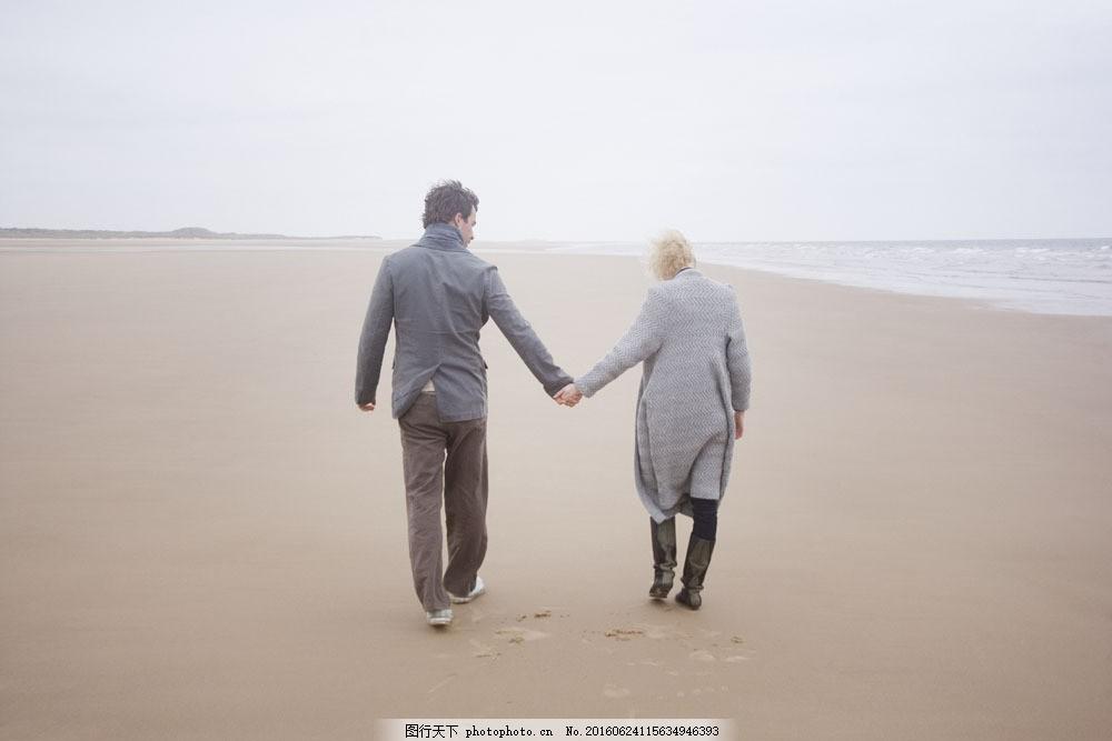 牵手走在沙滩上的情侣背影图片